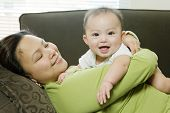 Mother Lying On Sofa Embracing Baby Boy (6-9 Months)