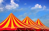 image of circus tent  - Circus tent red orange and yellow stripped pattern blue sky - JPG