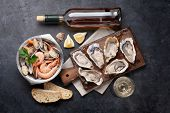 Fresh seafood and white wine on stone table. Oysters, prawns and shells. Top view poster
