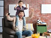 Father and son watching football on TV at home poster