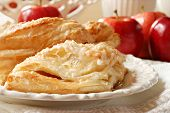 Delicious apple turnovers on decorative plate with fresh gala apples in background.  Closeup with sh