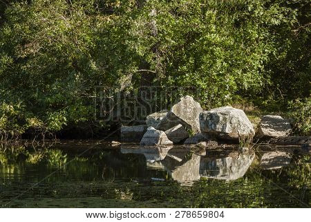 Pile Of Rocks Along Pond