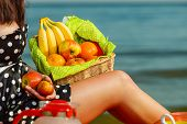 Woman Holding Picnic Basket With Fruits poster