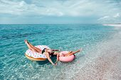 Mom with child chilling on lilo in the sea water. Family relaxing on inflatable rings on the beach.  poster
