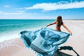 Girl relaxing on the beach, looking at sea landscape and holding boho pareo on the wind poster