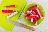 Crab Sticks In Green Glass Bowl, Crab Sticks, Kitchen Knife On Cutting Board On Wooden Table. Top Vi poster