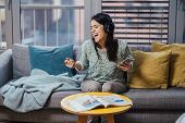 Cheerful woman listening to music with large headphones and singing.Music therapy,mood beneficial pr poster