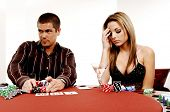 A sexy young couple playing out a hand of Texas Holdum laid out on a casino table Card backs are a d
