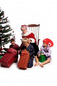 A group of children gathered around the Christmas Tree opening their gifts and Mrs. Santa Claus sitting in her rocking chair.