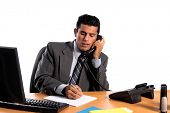 Handsome young business man in a grey suit at his desk talking on the telephone