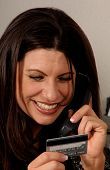 Close up detail of a happy business woman on her office phone making a payment with a credit card