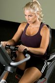 Beautiful blond woman during a cardio workout on a recumbent exercise bike in the gym
