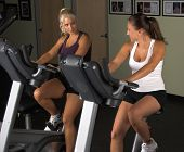 Two women during a cardio workout on an exercise bikes in the gym