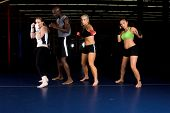 Three beautiful young woman fighters shadow boxing with their trainer in an MMA gym