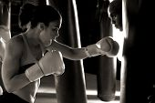 Serious female boxer throwing a right cross at the heavy bag being held by her trainer while he look