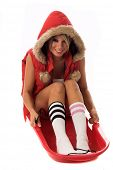 Beautiful young girl in lingerie and a red parka with a fur trimmed hood in a red snow sled