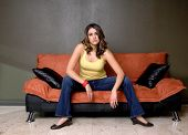 pic of wife-beater  - Pretty young Mexican woman in jeans and a yellow wife beater casually sitting on a black and orange couch - JPG