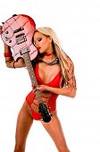Sexy young blonde lingerie model in a red one piece and red high heels with a red Les Paul style electric guitar