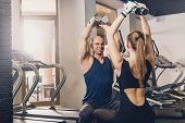 A Man And A Woman Are Training With Dumbbells. Physical Exercise With Dumbbells Two People For The S poster