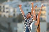 Excited Couple Celebrating Vacation Raising Arms In A Town At Sunset poster