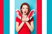 Surprised Redhead Girl In Red Dress With Gumshoes On Blue Background. poster