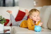 Little Boy Looks On Moneybox And Plans Of What He Can Buy. Teaching A Child How To Handle Money. Mon poster