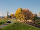 Golf In Fall With Men Driving Carts To The Fairway
