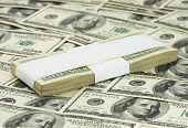 stock photo of ten thousand dollars  - ten thousand dollars lying on heap of banknotes - JPG