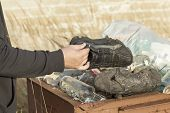 Homeless find the footwear in waste container