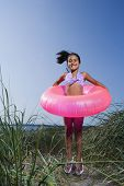 Little girl with inner tube on beach