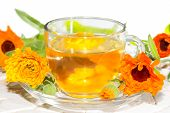 image of home remedy  - Herbal tea made from Calendula officinalus or the Pot Marigold with fresh orange flowers used as a colourant in cookery and as a bactericide anti - JPG