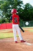 foto of little-league  - Little league boy getting the sign from the coach before batting - JPG