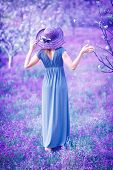 Dreamy, fine art photo of seductive woman in fairy garden, romantic girl in elegant long dress on purple lavender field, sensual nymph in the forest