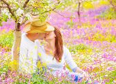 Cute young family sitting down on pink floral meadow in the garden and kissing, woman and man enjoyi