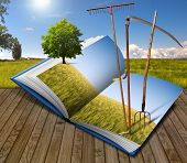 image of scythe  - Open book with agricultural landscape and rake scythe and pitchfork - JPG