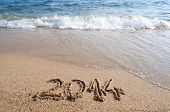 Year 2014 handwritten on the sandy beach and waves coming