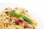 Spaghetti carbonara with fried bacon and basil isolated on white