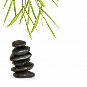 image of spa massage  - Zen abstract of spa massage stones in perfect balance with bamboo leaves over white background - JPG