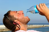 A Man Thirsty Eagerly Drinking Water From Plastic Bottle