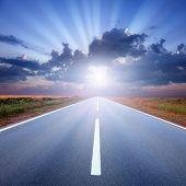 Driving On Asphalt Road Towards The Sunbeams