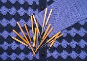 stock photo of knitwear  - Heap of hooks for knitting scattered on the surface blue knitwear - JPG