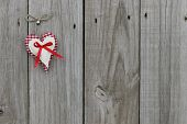 Red gingham and muslin hearts hanging on wood background