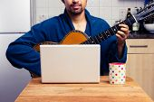 Man Teaching Himself To Play Guitar At Home