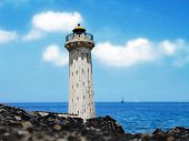 Idle lighthouse before blue sea