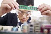 stock photo of protective eyewear  - young asian man fixing computer with protective eyewear - JPG