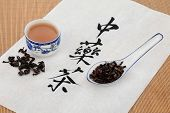 Oolong herb with chinese herbal tea calligraphy script and teacup over rice paper and bamboo backgro