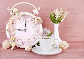 Beautiful vintage alarm clock with flowers and cup of tea on pink wooden background