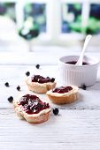 Fresh bread with homemade butter and blackcurrant jam on wooden table, on bright background