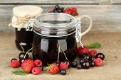 Tasty jam with berries in glass jars on wooden table