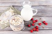 Homemade granola in glass jar, fresh cherries and jug with milk on color wooden background